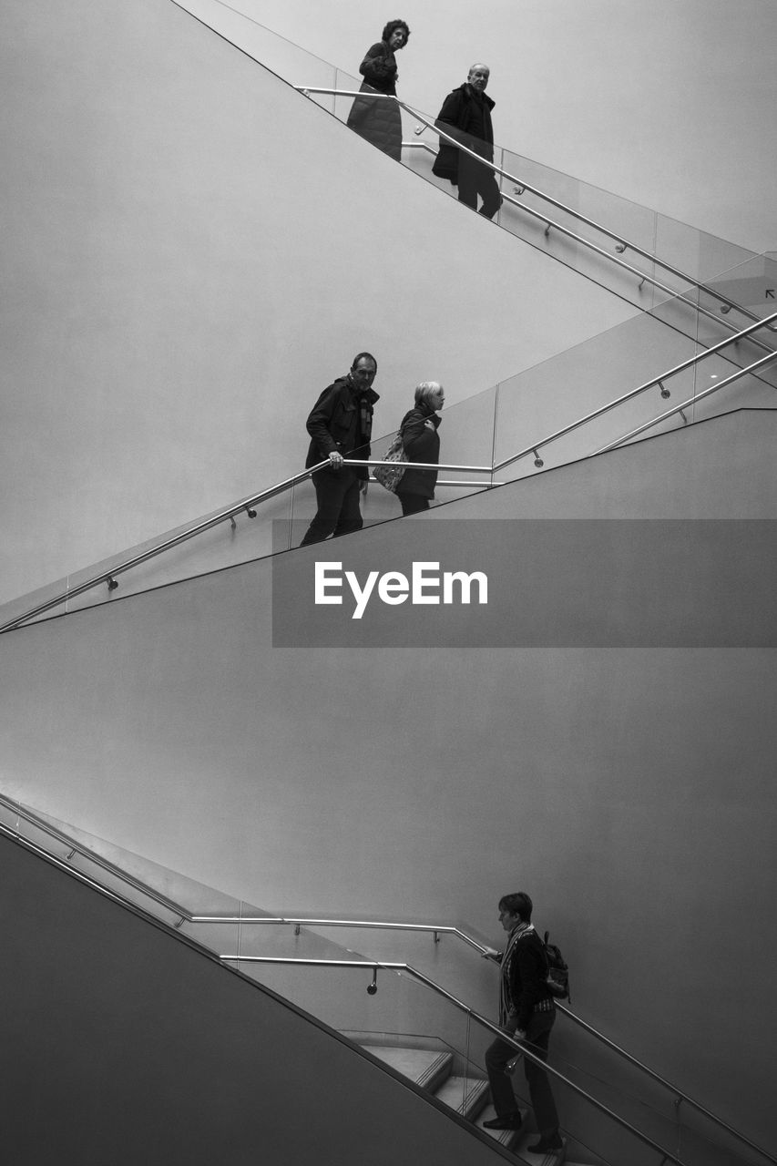 LOW ANGLE VIEW OF PEOPLE WALKING ON STAIRCASE