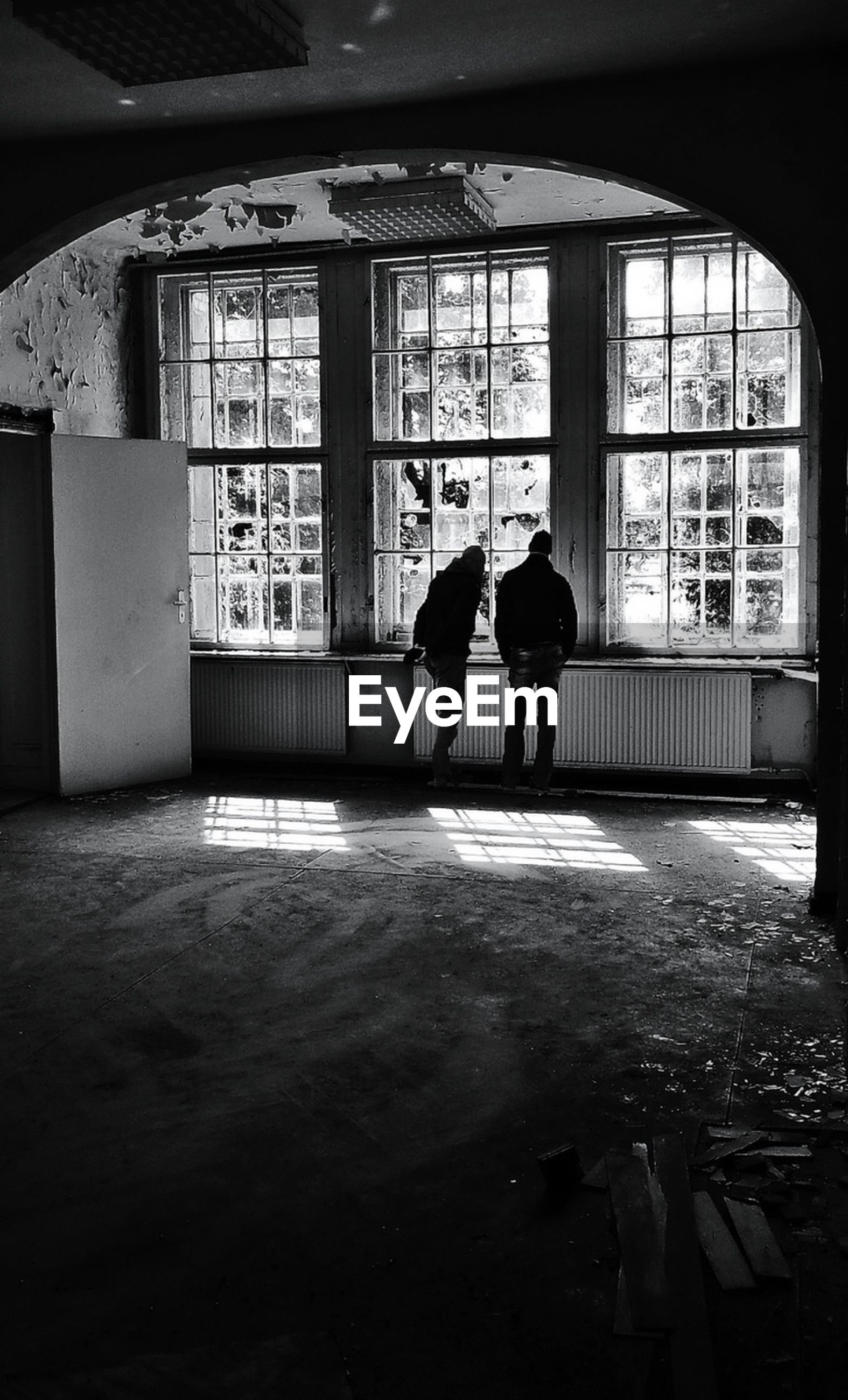 Rear view of two people in an empty room