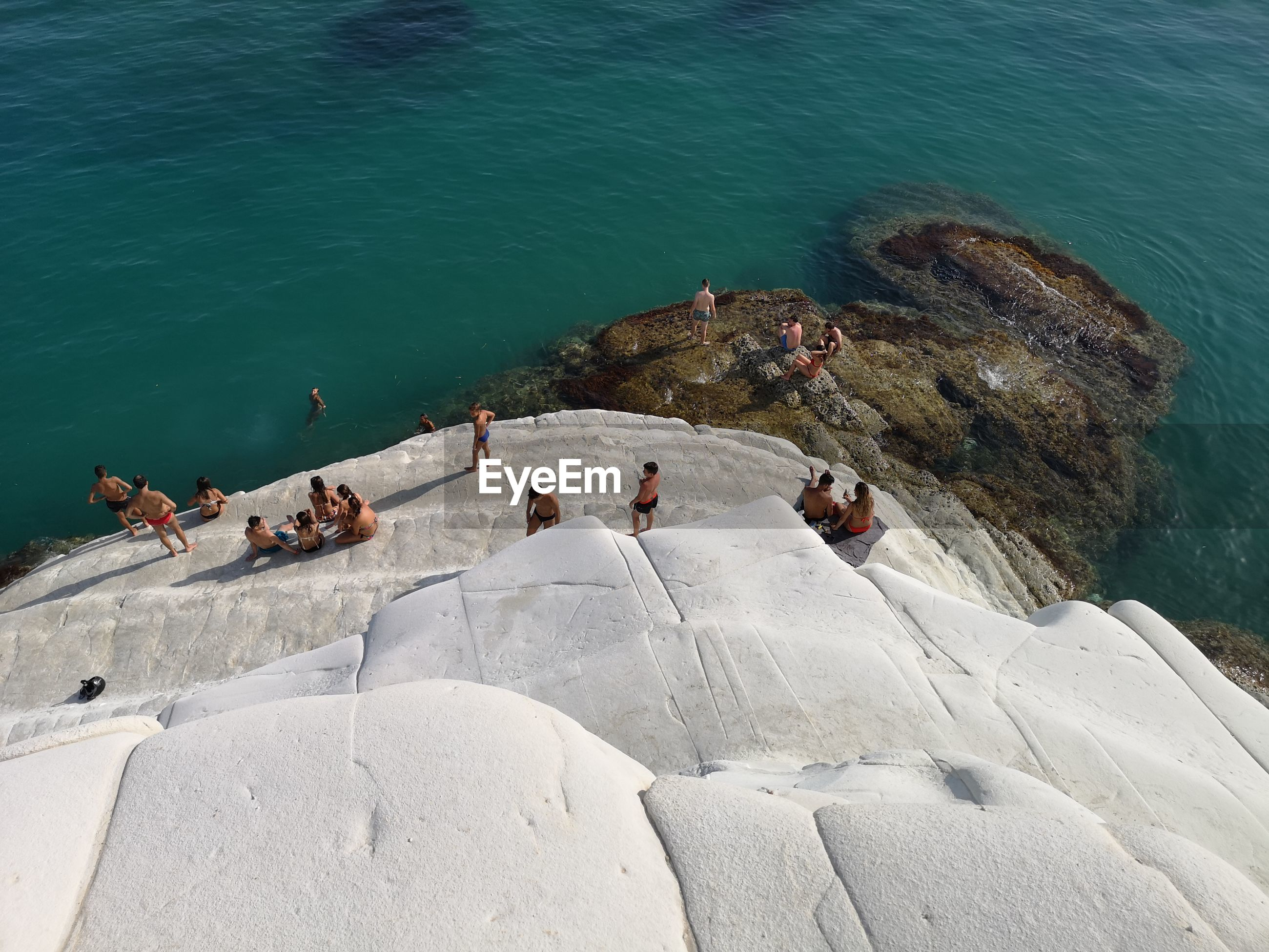 HIGH ANGLE VIEW OF GROUP OF PEOPLE ON ROCKS BY SEA