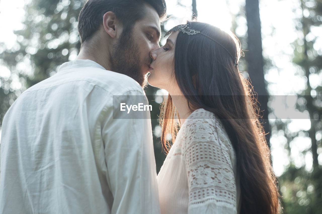 two people, togetherness, real people, love, couple - relationship, young women, young men, young adult, emotion, bonding, lifestyles, women, positive emotion, adult, heterosexual couple, men, side view, leisure activity, casual clothing, tree, outdoors, hairstyle