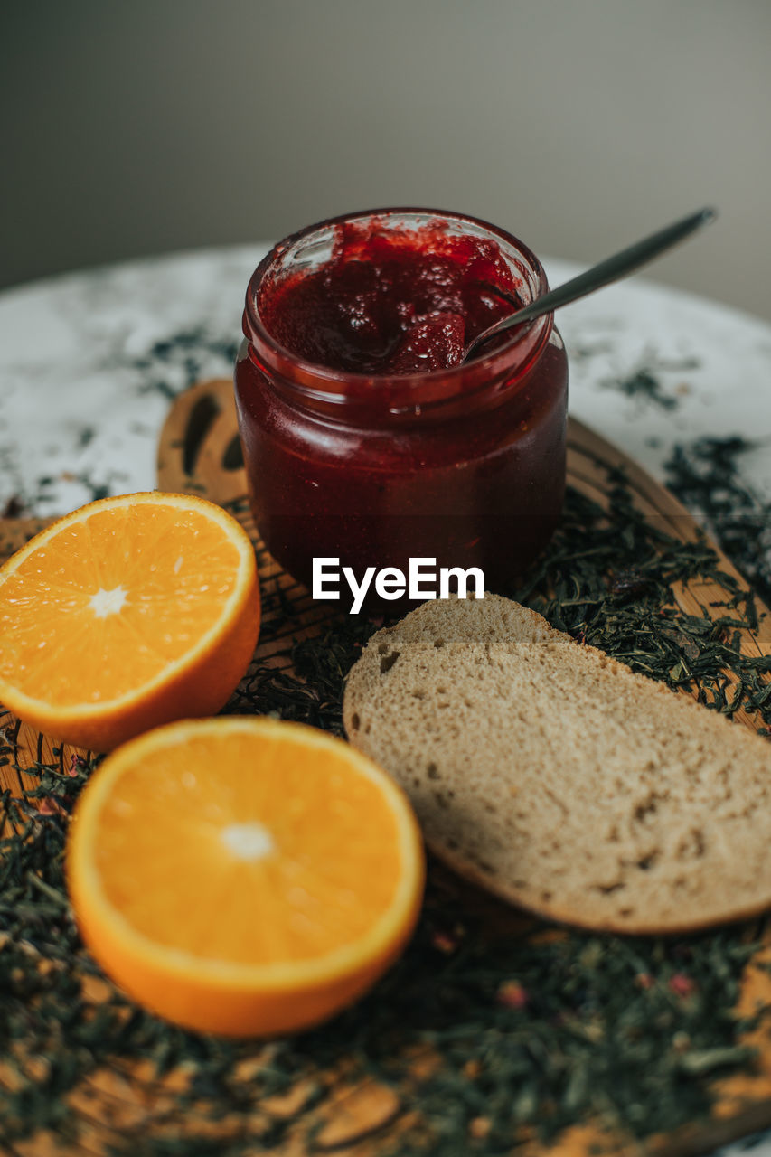 Close-up of orange and jam in jar on table