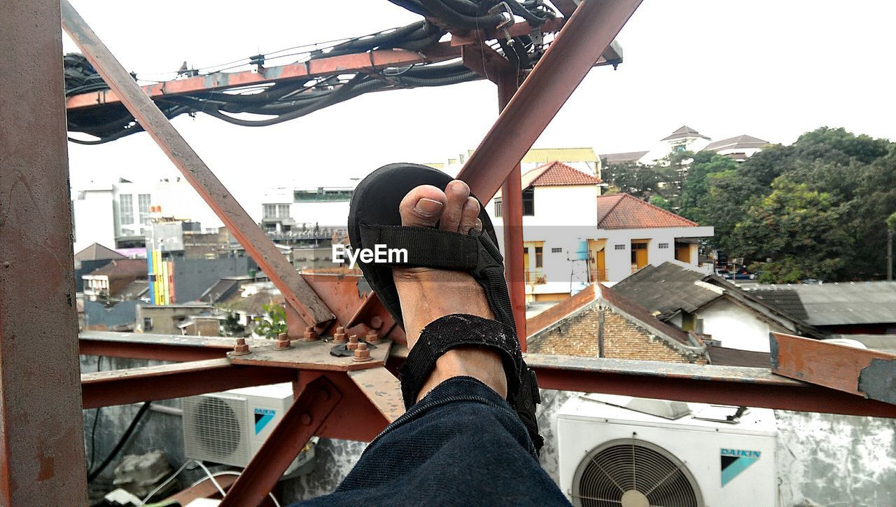 Cropped image of leg on metal railing in balcony