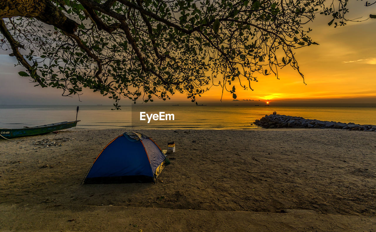 sunset, water, sky, tree, beauty in nature, scenics - nature, plant, land, nature, sea, beach, tranquility, orange color, tranquil scene, tent, transportation, nautical vessel, outdoors, idyllic, horizon over water, no people