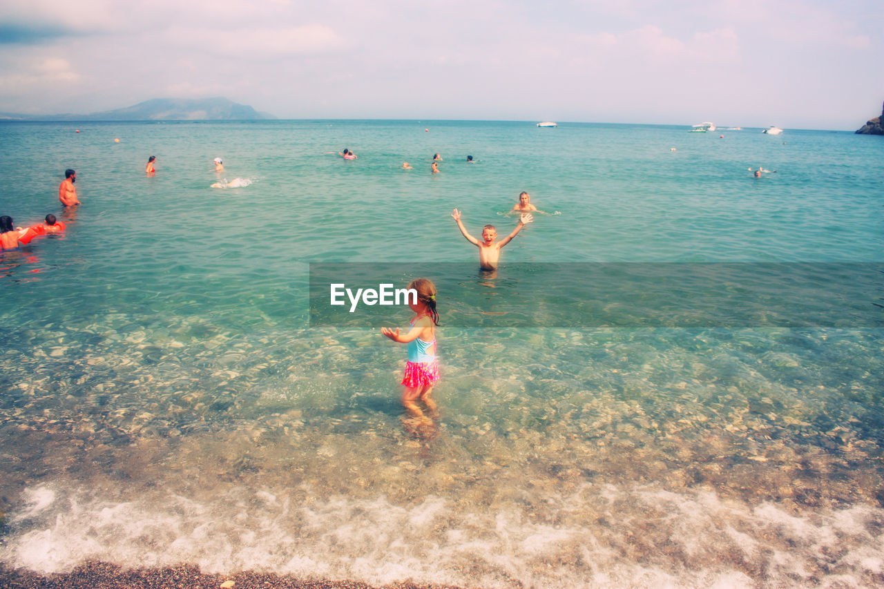 sea, horizon over water, two people, real people, beach, leisure activity, water, nature, sky, vacations, full length, enjoyment, fun, day, beauty in nature, outdoors, lifestyles, scenics, childhood, girls, adventure, standing, togetherness, swimming, people