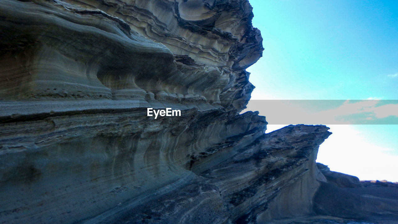 rock formation, geology, physical geography, nature, rock - object, beauty in nature, day, sky, outdoors, no people, low angle view, tranquility, tranquil scene, scenics, textured, landscape, travel destinations, mountain, close-up