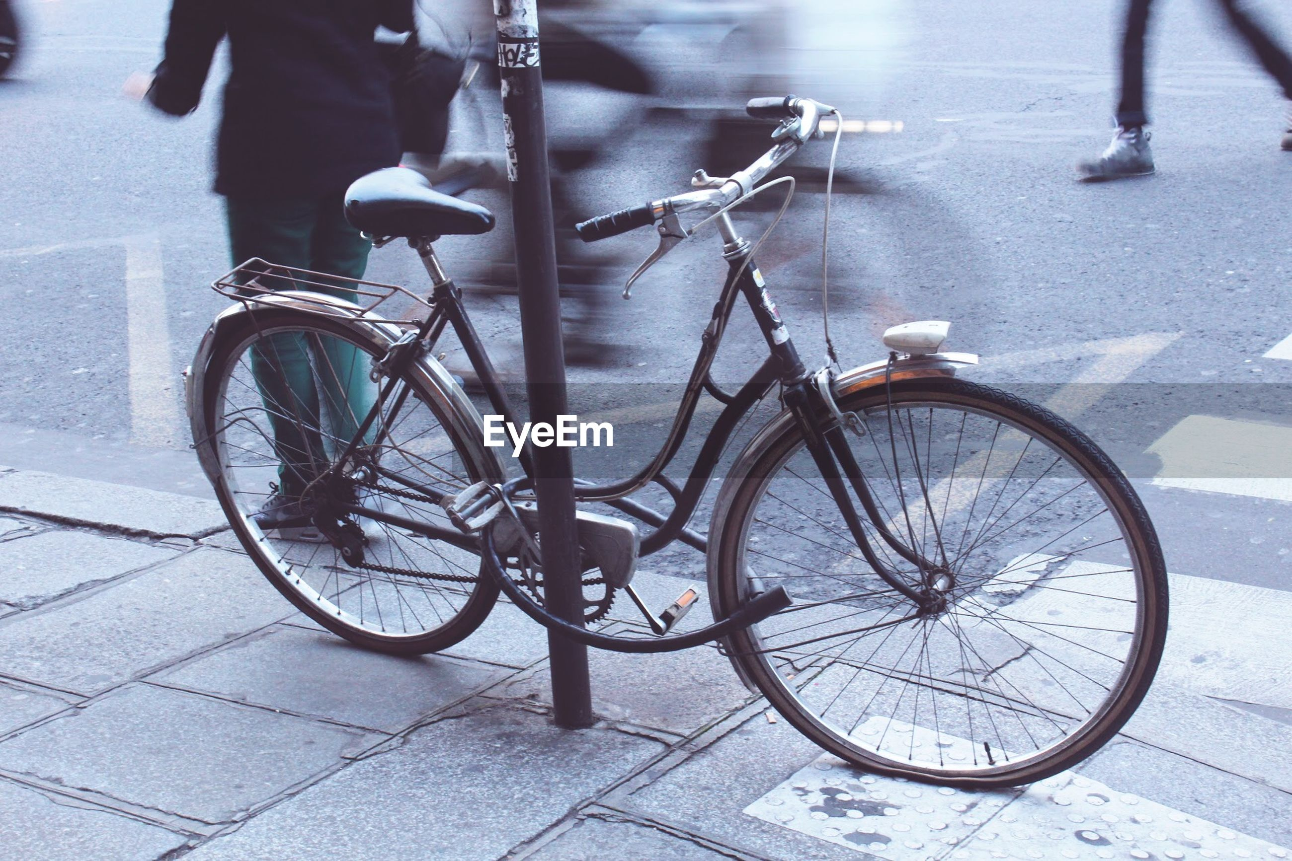 Side view of parked bicycle against pole