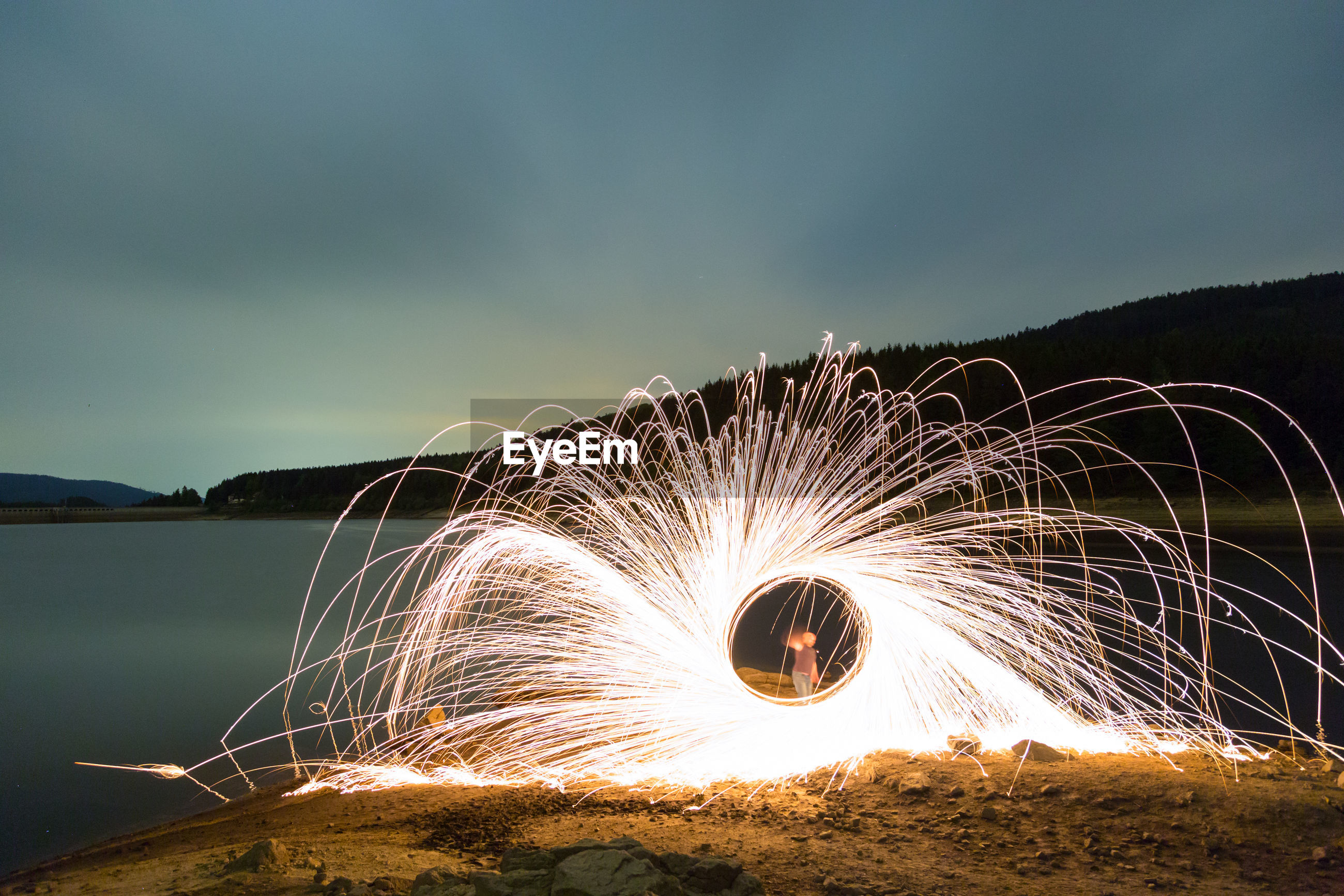 Man spinning illuminated wire wool by lake against sky at night