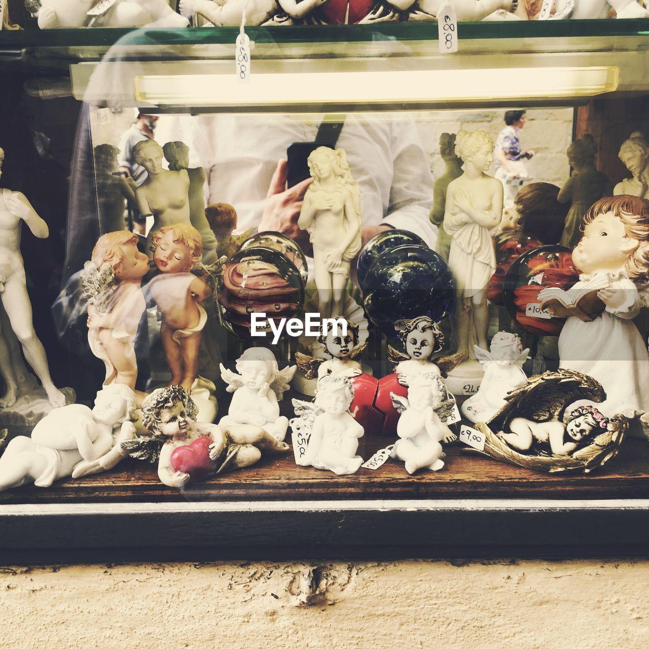 Figurines On Window Display Of Store