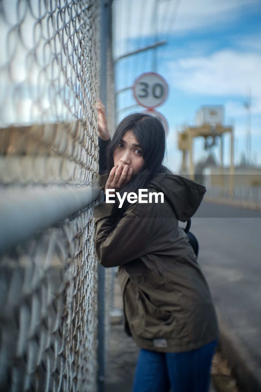 Portrait Of Woman Standing By Fence In City