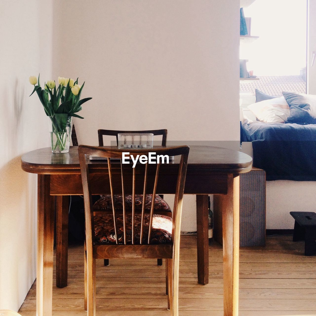 Vase on table with chairs in a room