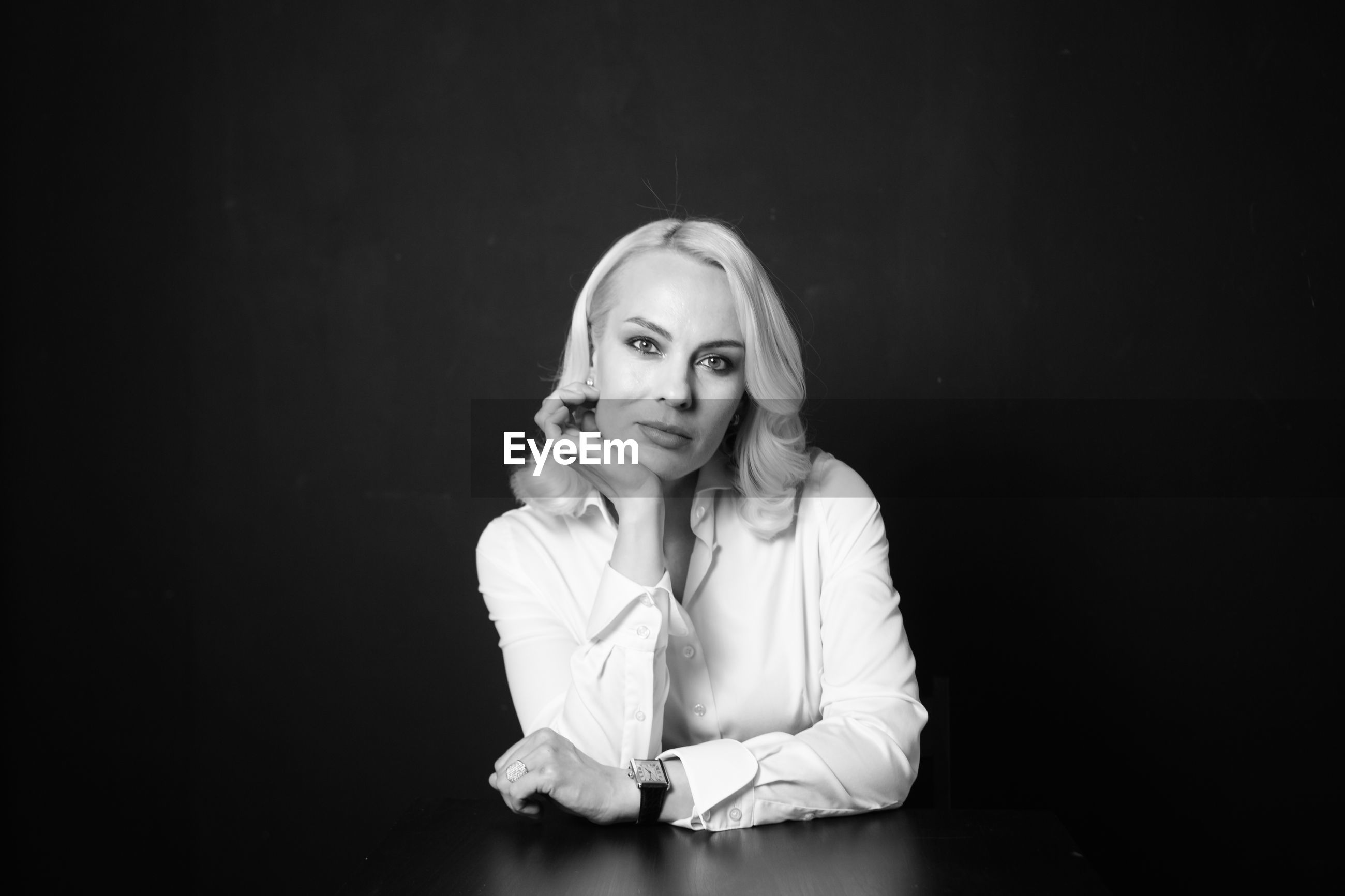 Portrait of businesswoman sitting by table against wall