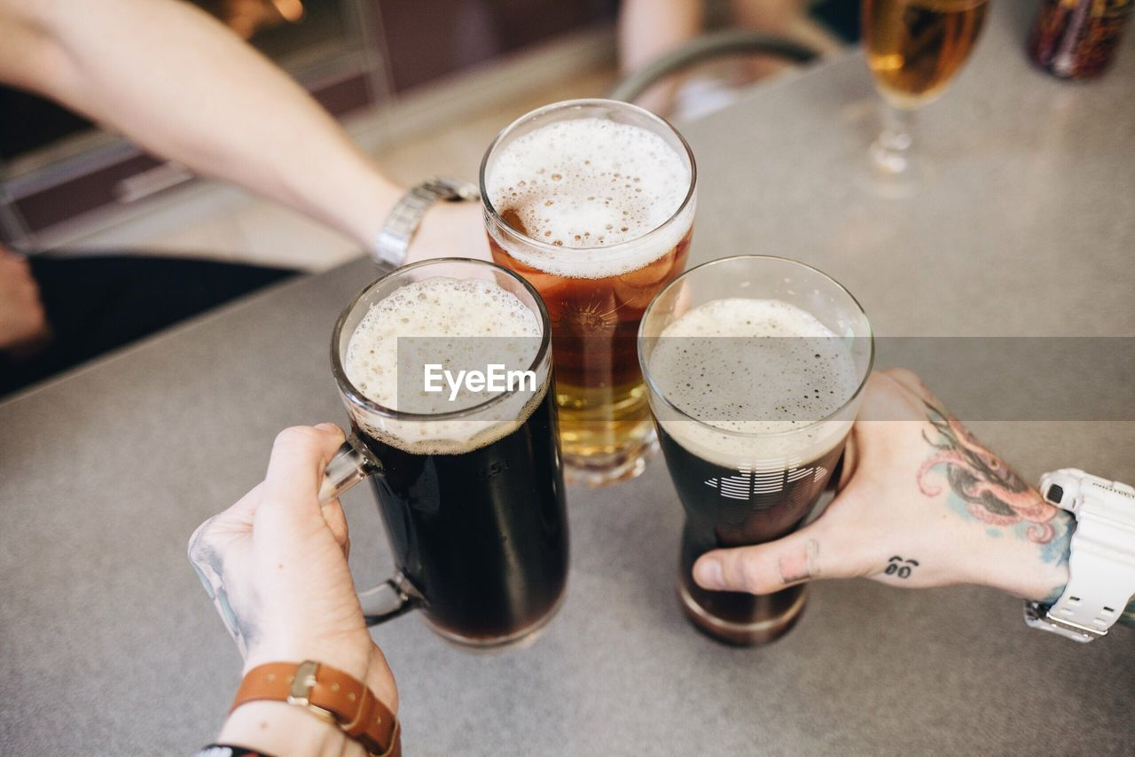 Close-Up Of Hands Holding Beer Glass