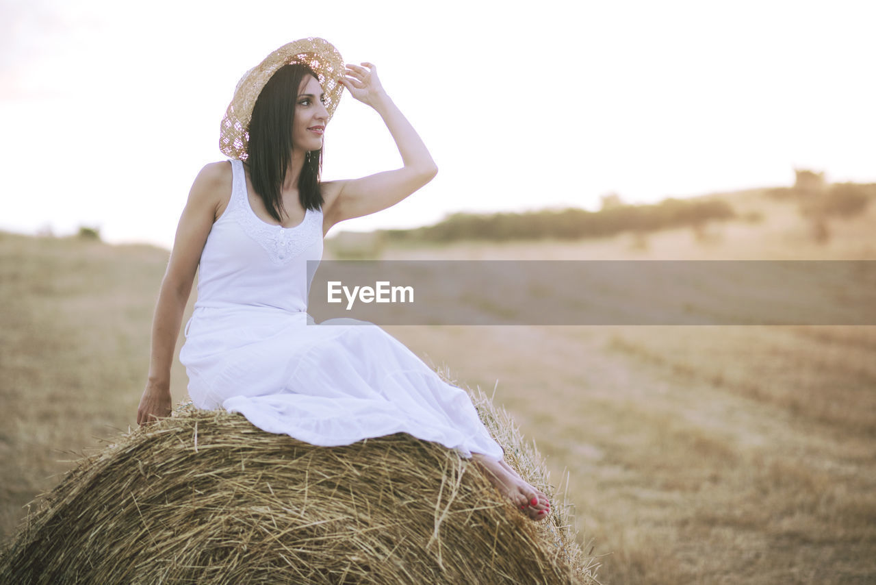 Smiling Young Woman Sitting On Hay Bale At Field Against Clear Sky