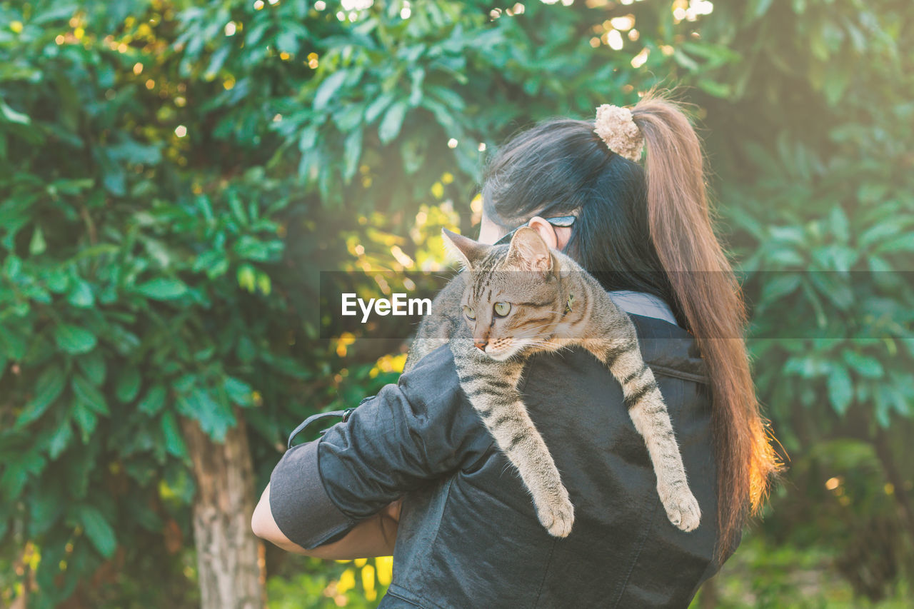 Portrait of young woman carrying cat