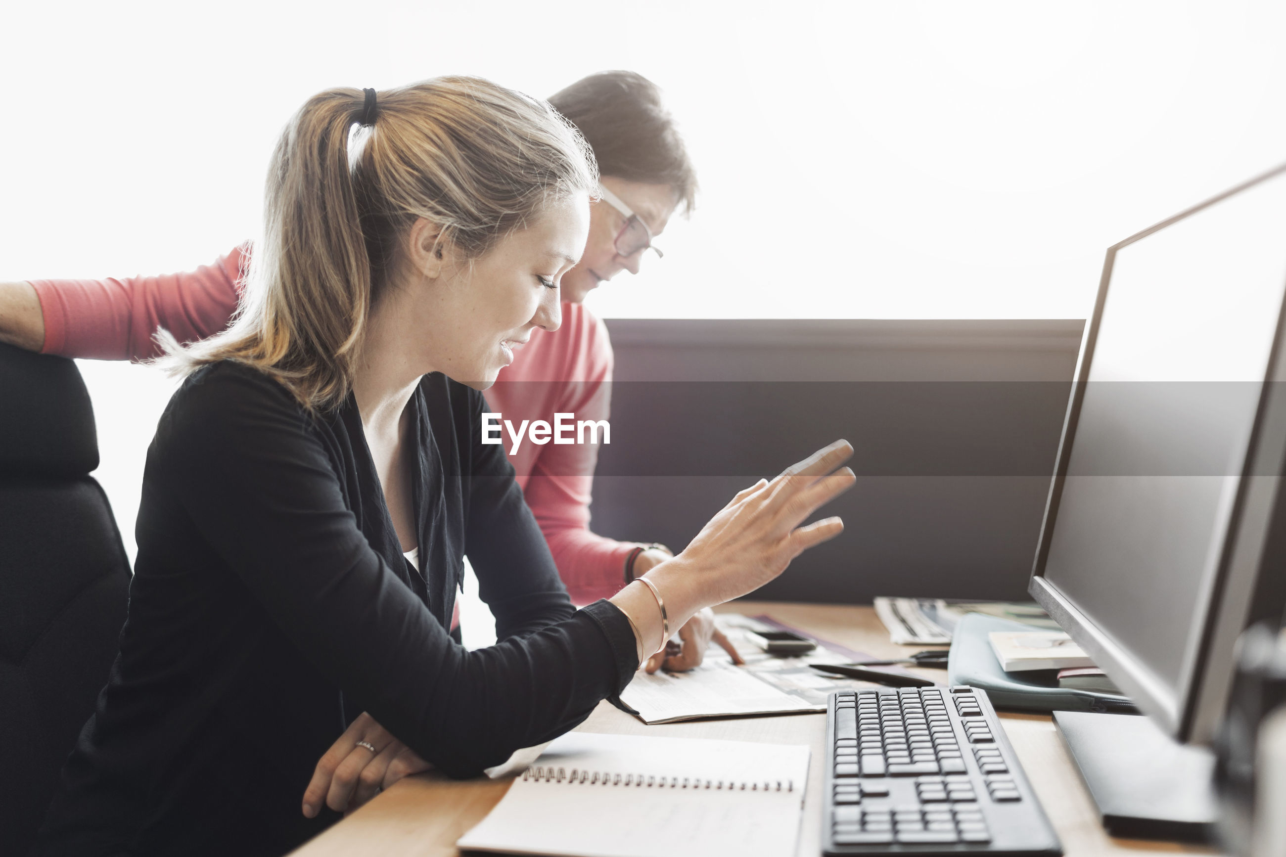 WOMAN USING MOBILE PHONE WHILE SITTING IN OFFICE