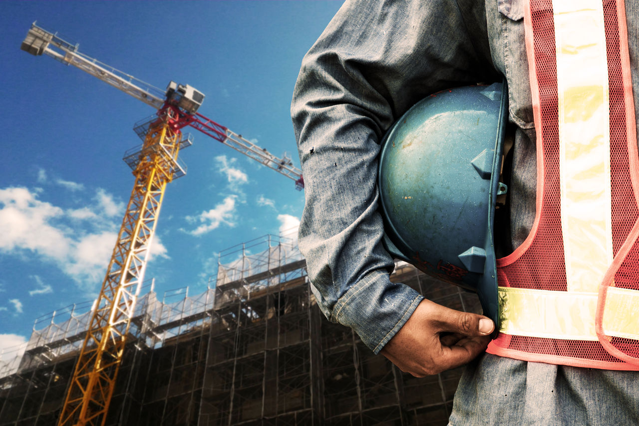 Midsection Of Engineer With Helmet Standing At Construction Site