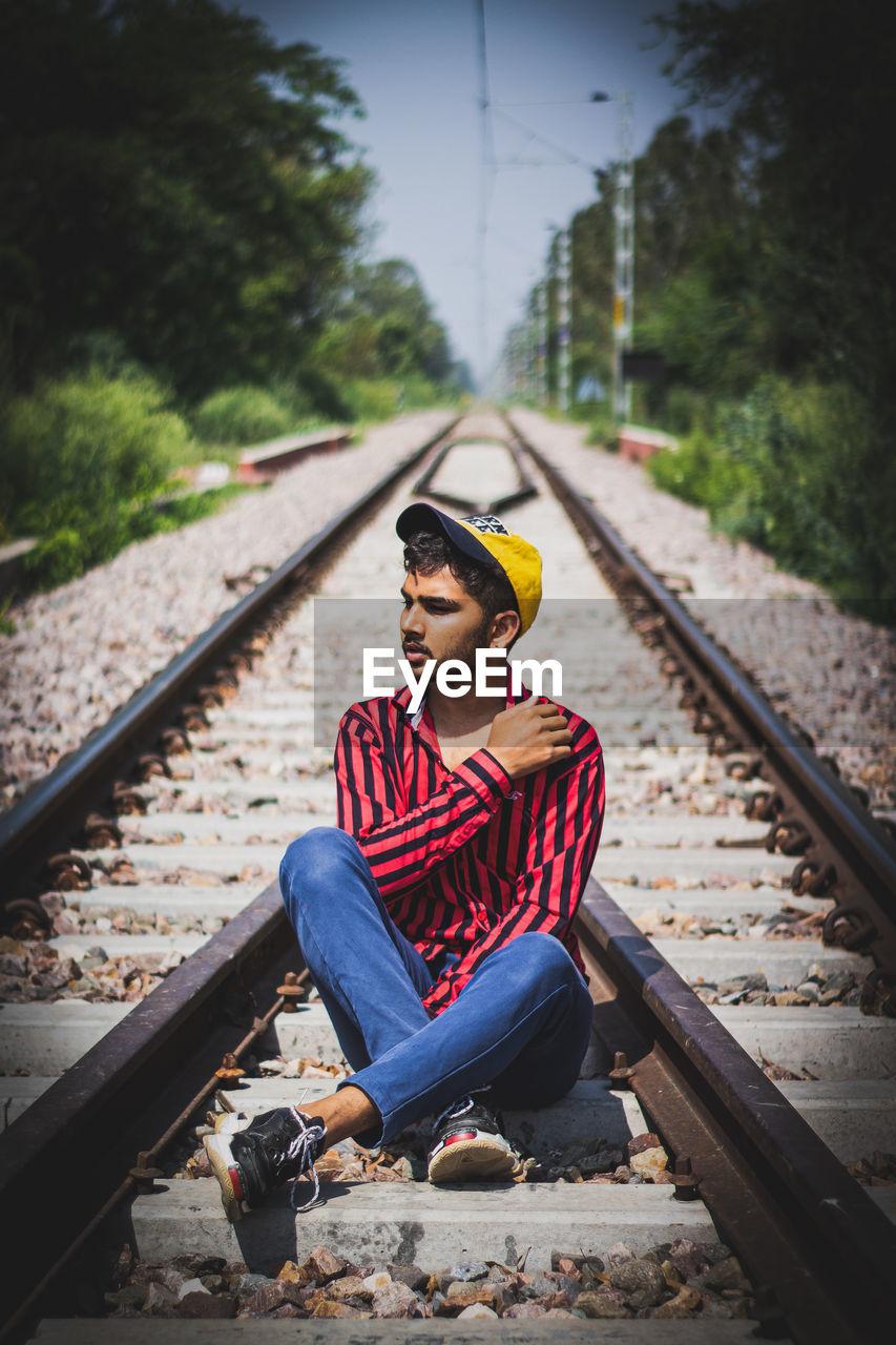Man sitting on railroad track