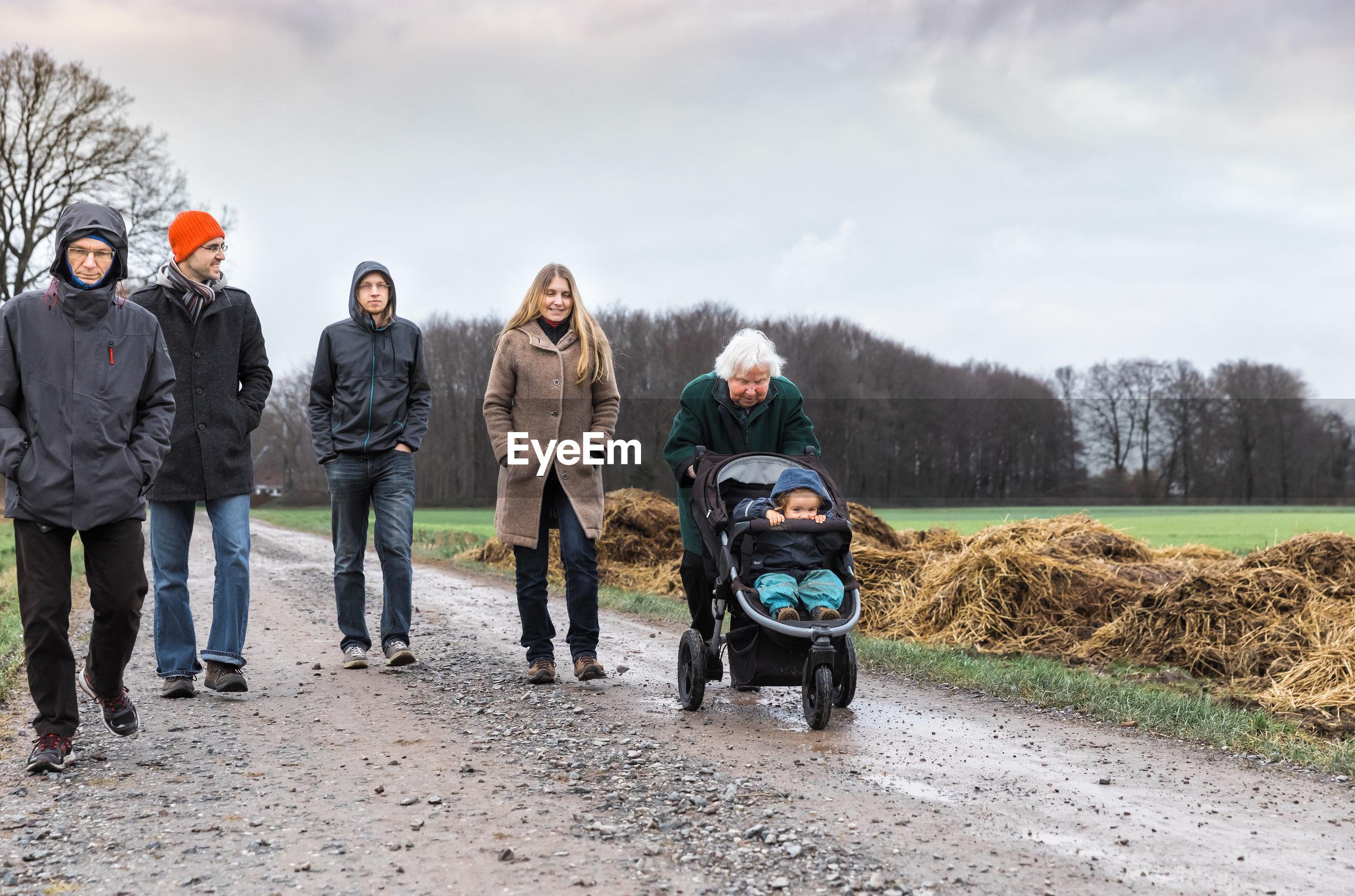 Family walking on dirt road against sky