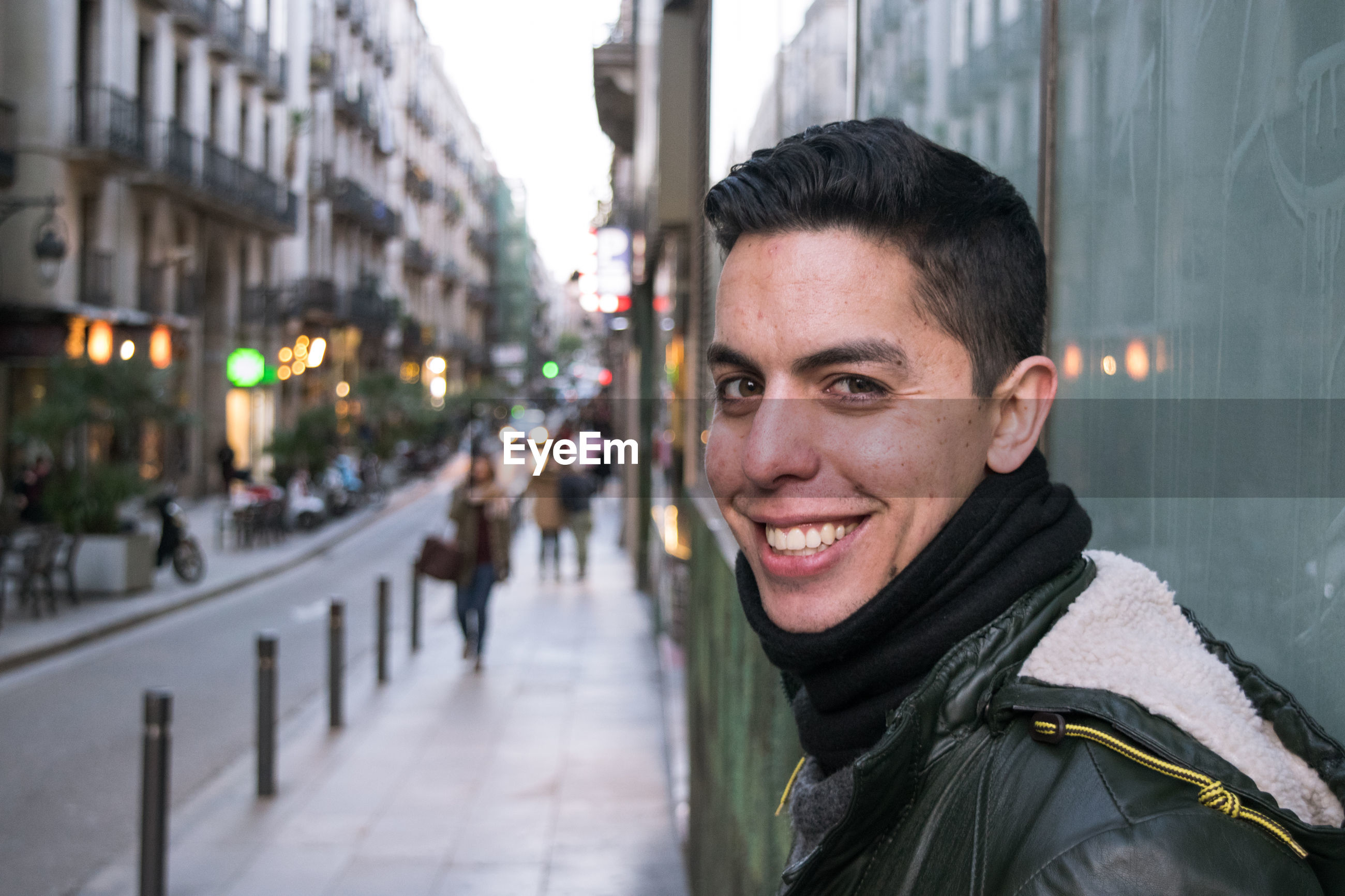 Portrait of smiling man on street in city at dusk
