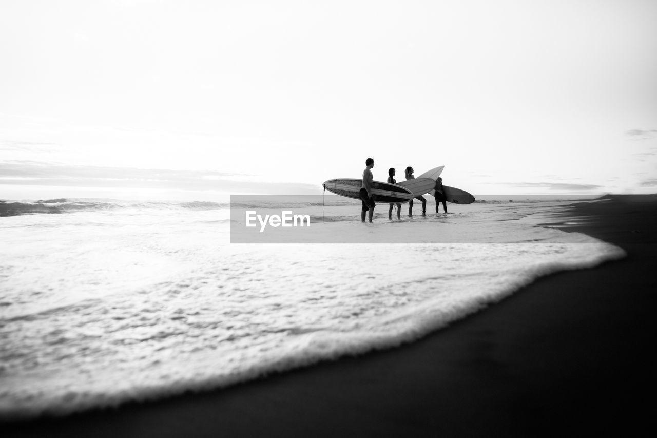 MEN SITTING ON CHAIR AT BEACH