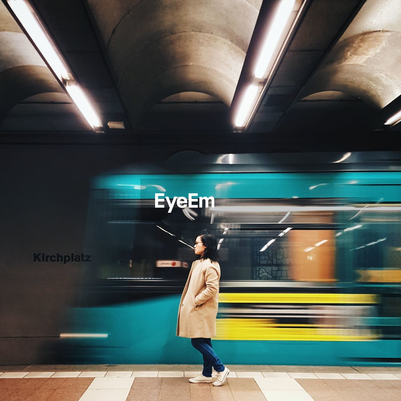 Side View Of Woman Standing Against Train At Illuminated Subway Station