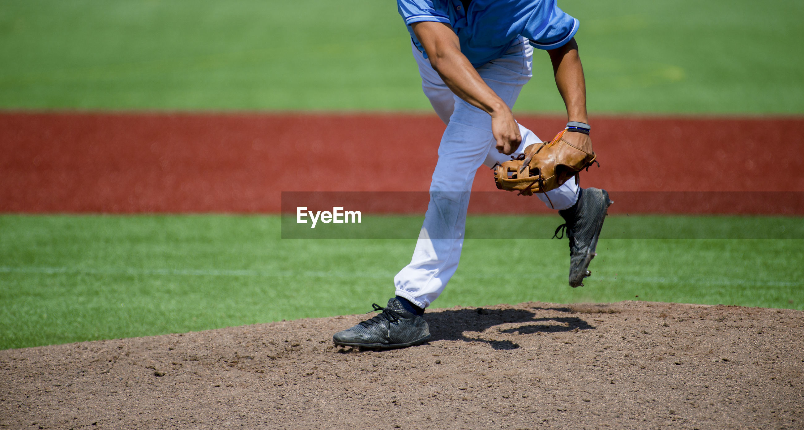 Low section of man playing baseball on field