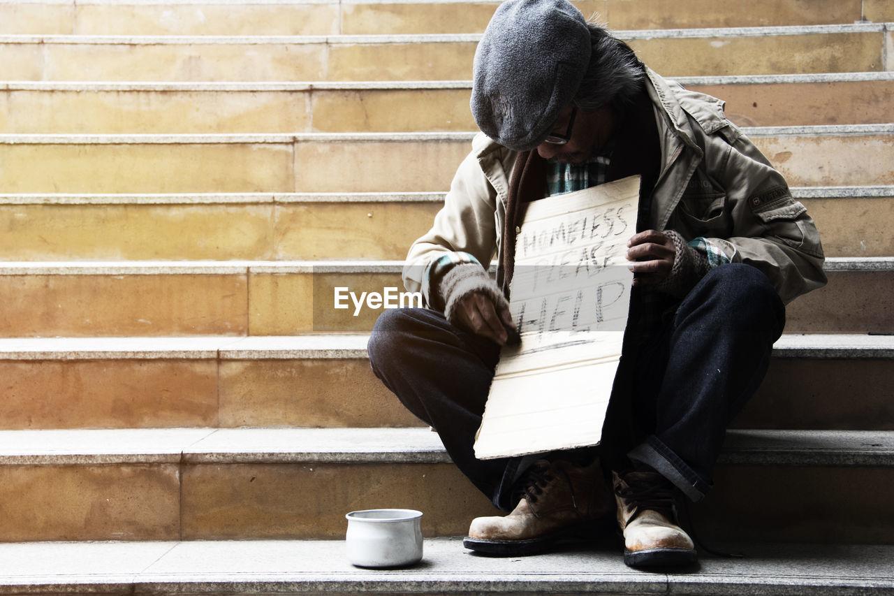 Male beggar begging while sitting on steps