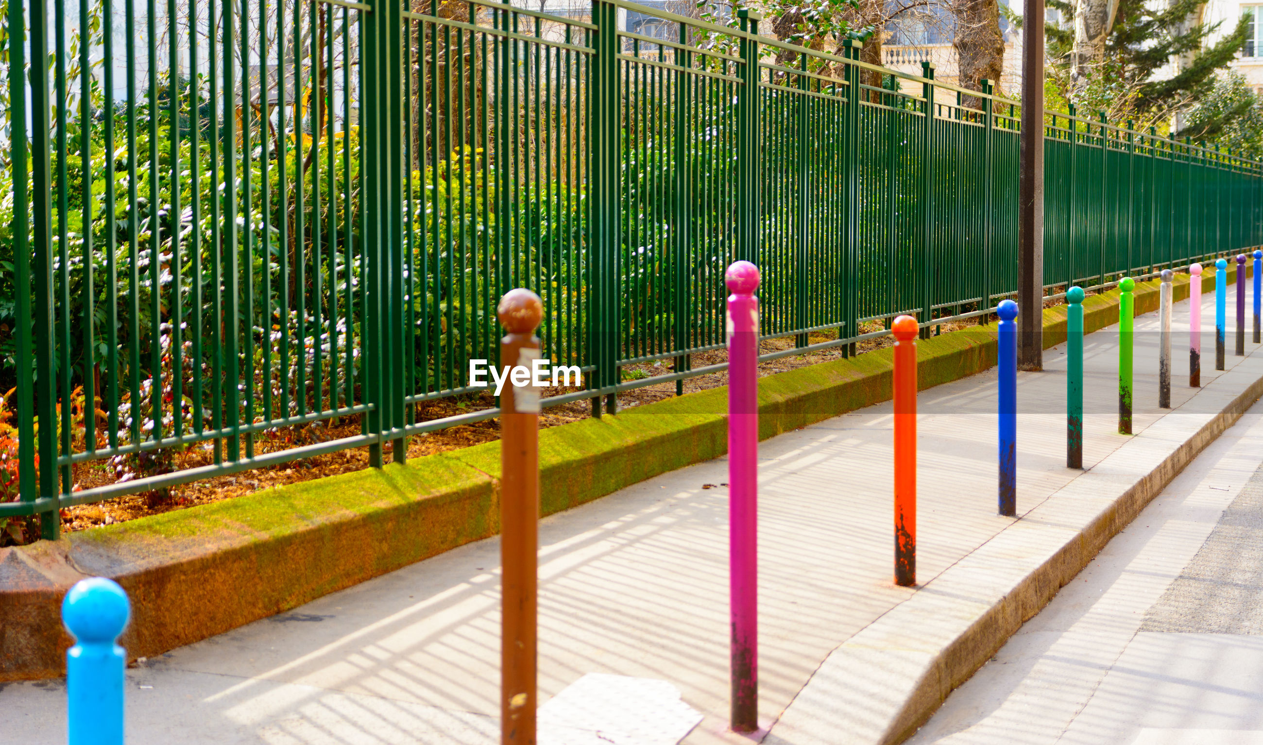 Colorful bollards on footpath along fence