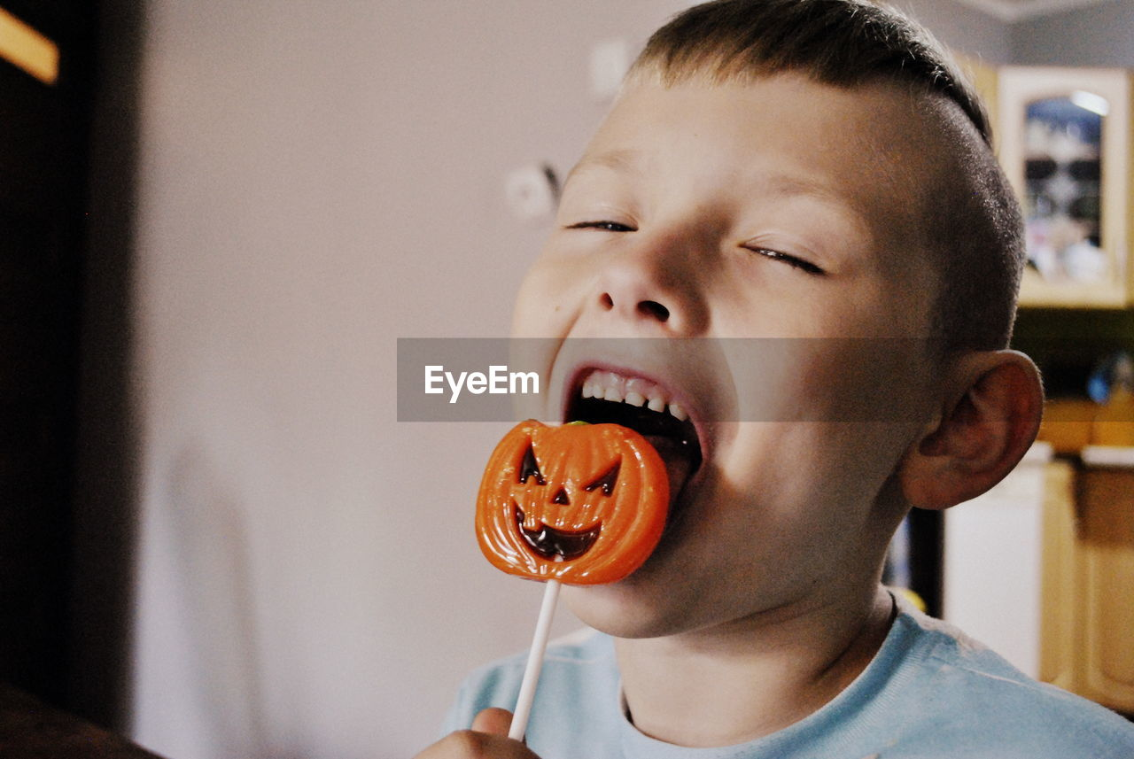 Portrait Of Happy Boy Licking Halloween Lollipop At Home