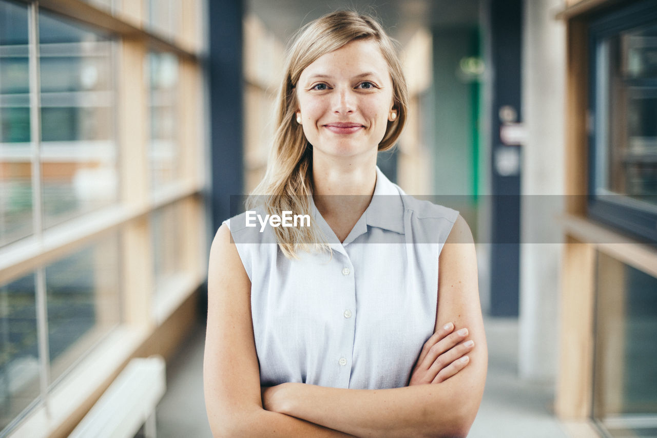 Portrait of confident woman with arms crossed standing in lobby