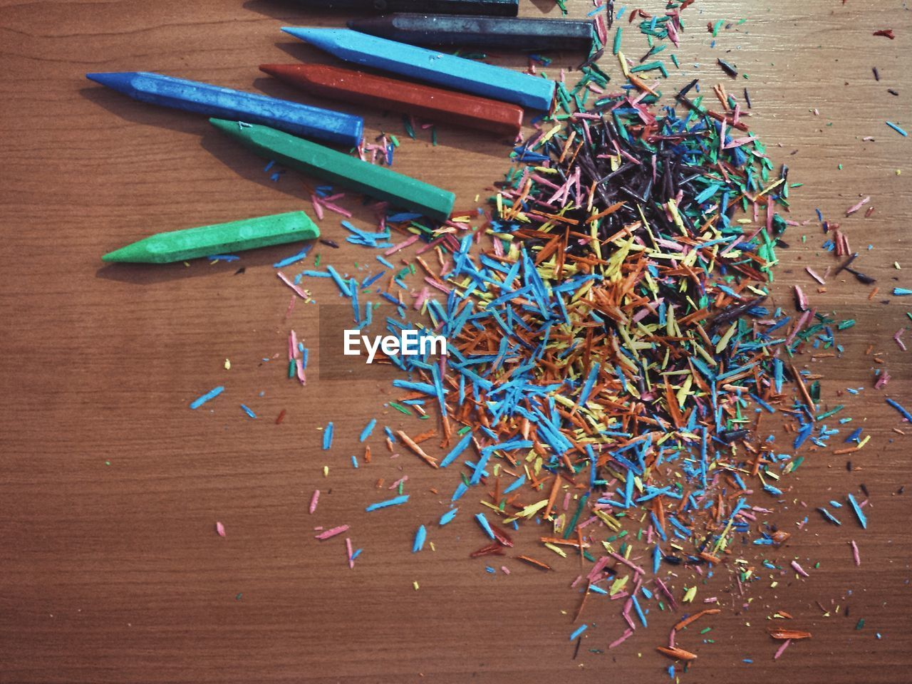 Directly above view of colorful crayon shavings on table