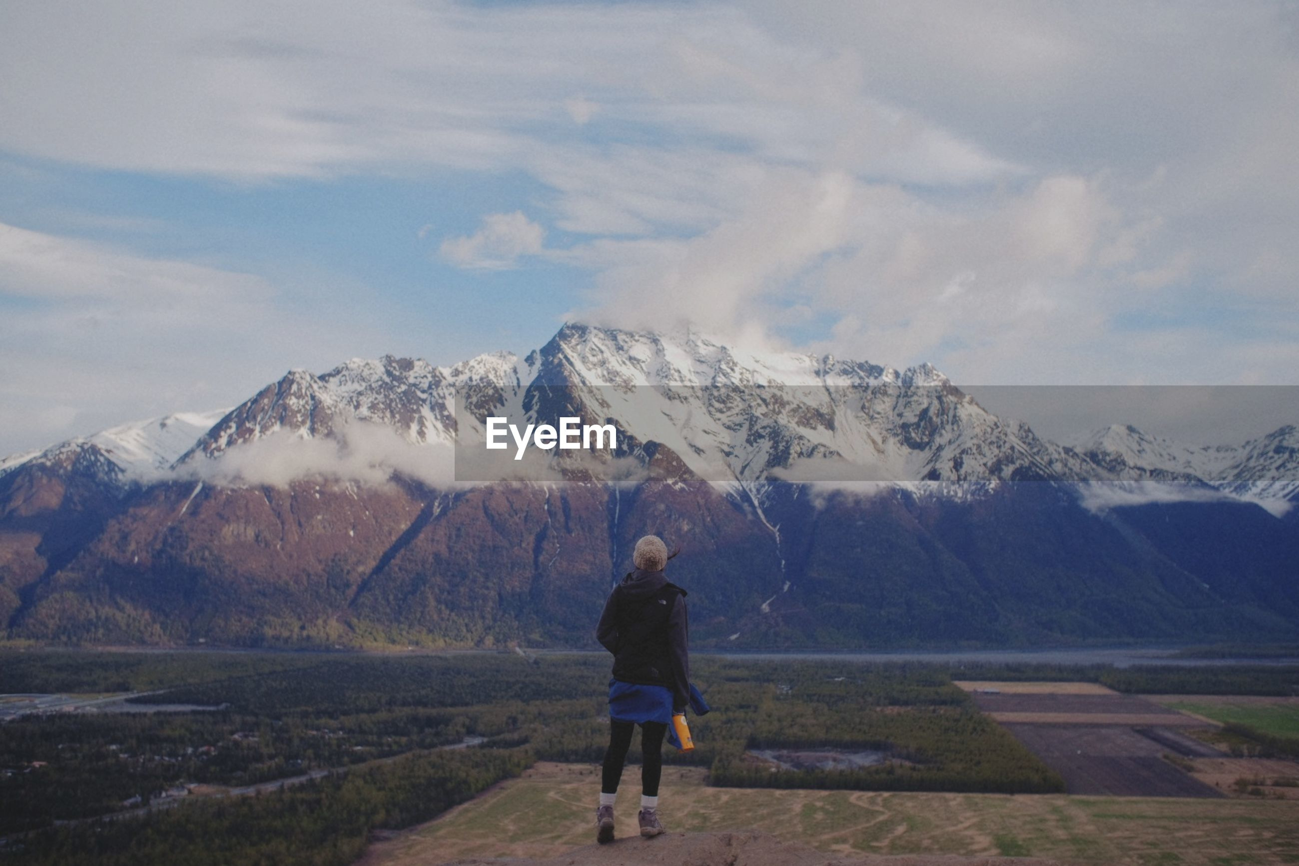 Full length rear view of woman looking at snowcapped mountains against sky