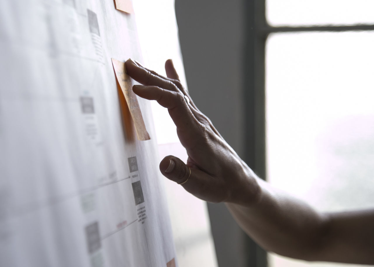 Cropped Hand Of Woman Touching Adhesive Note On Whiteboard