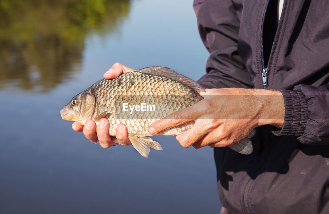 Midsection Of Man Holding Fish By Lake