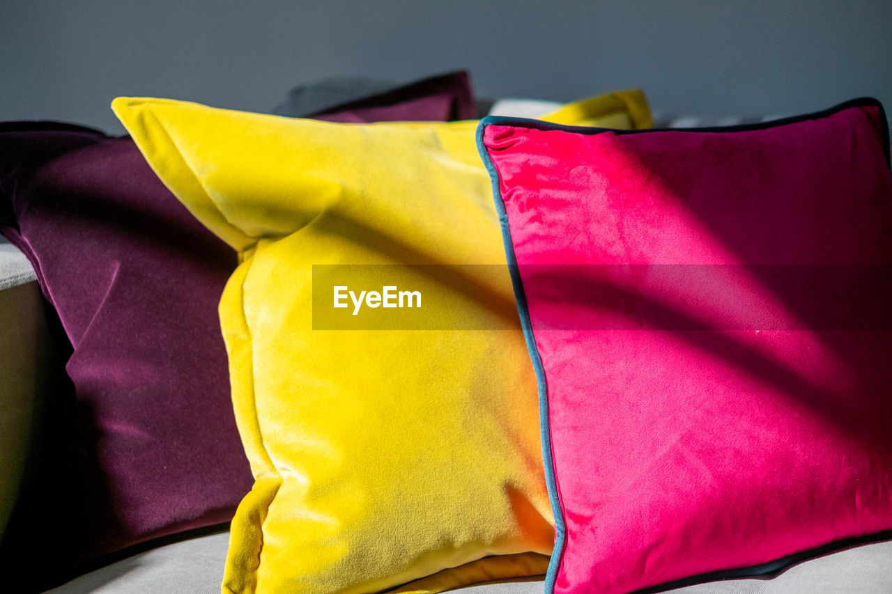 Close-up of multi colored cushions on bed