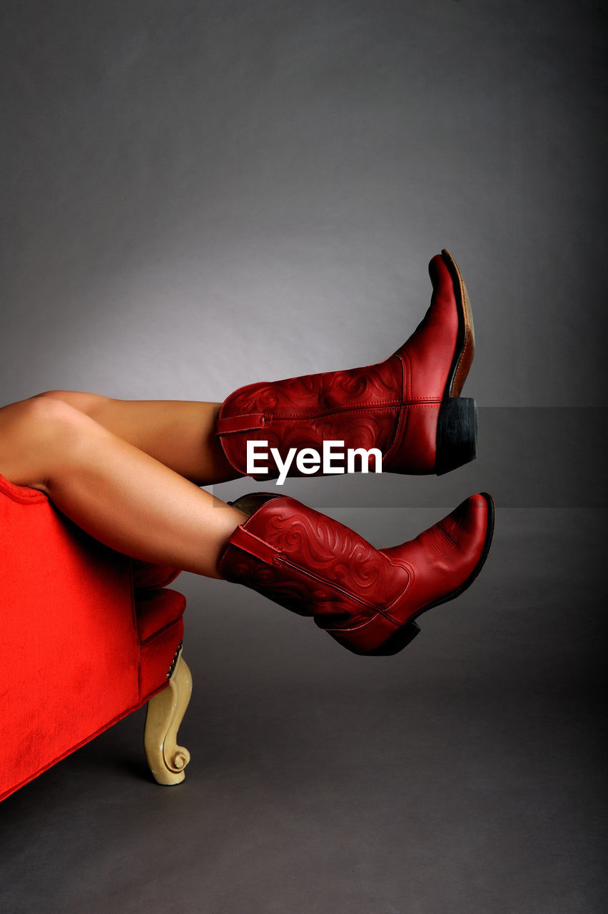 Low Section Of Woman Wearing Red Shoes Against Gray Background
