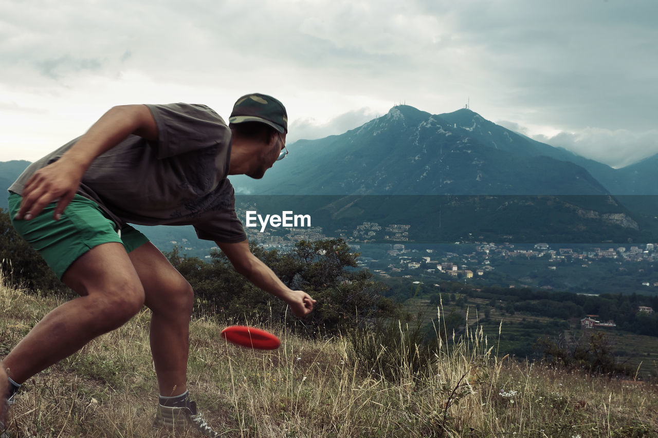 Man throwing plastic disc on field against mountain