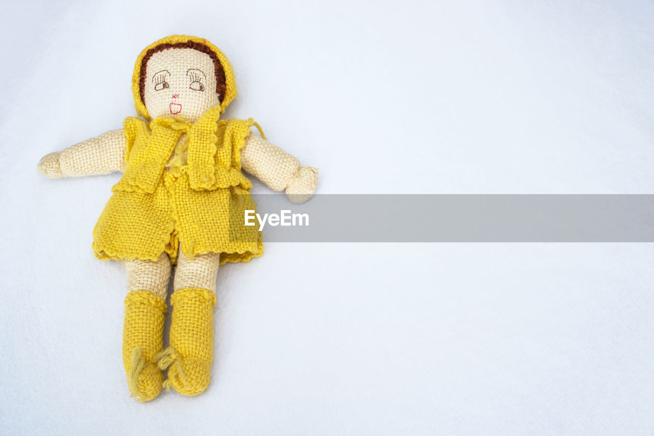 Close-up of yellow doll against white background