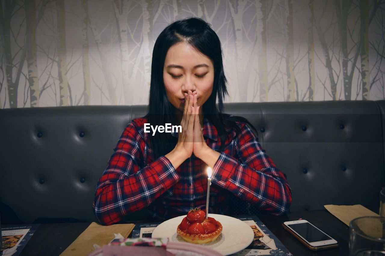 Young Birthday Woman Praying In Front Of Illuminated Candle On Strawberry Tart At Restaurant