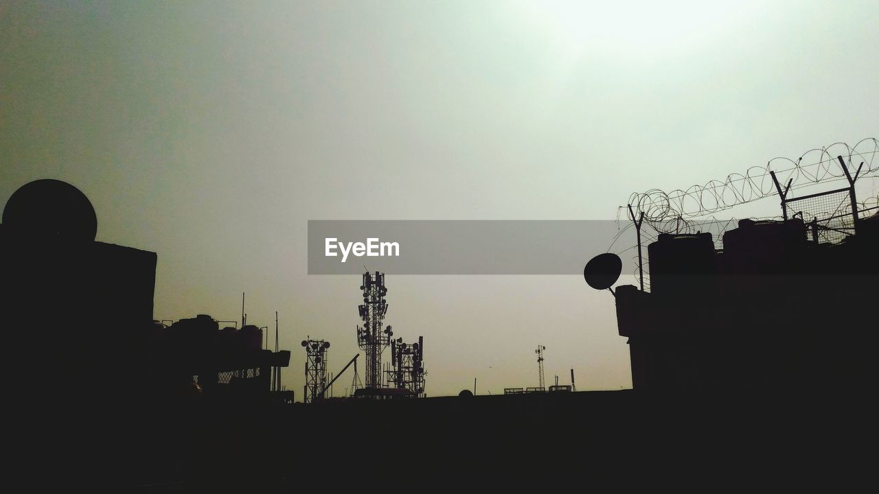 sky, built structure, silhouette, low angle view, architecture, nature, technology, building exterior, sunset, connection, no people, communication, outdoors, clear sky, industry, copy space, sun, building, construction industry, broadcasting, power supply