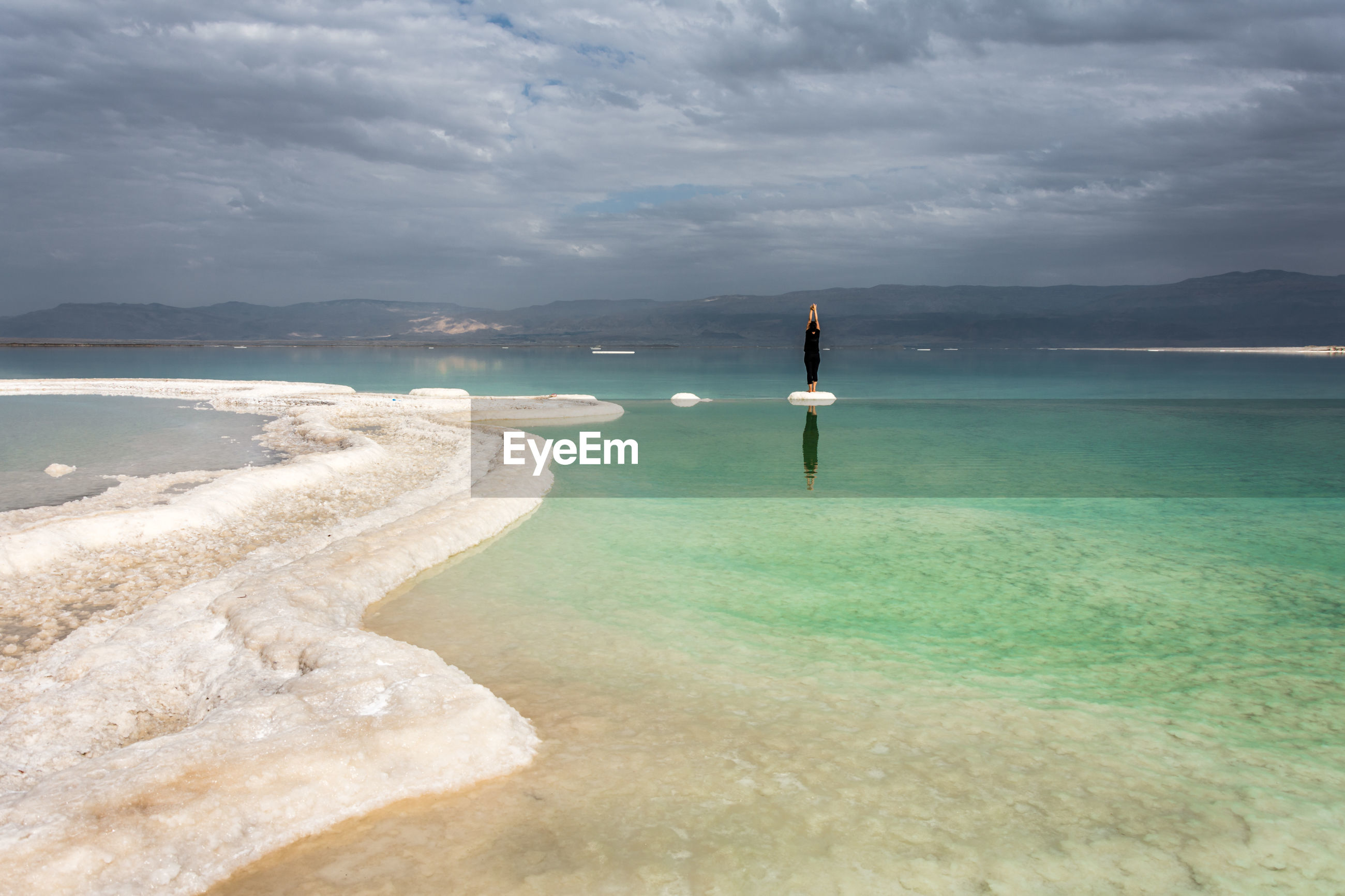 Rear view of woman practicing at dead sea against cloudy sky
