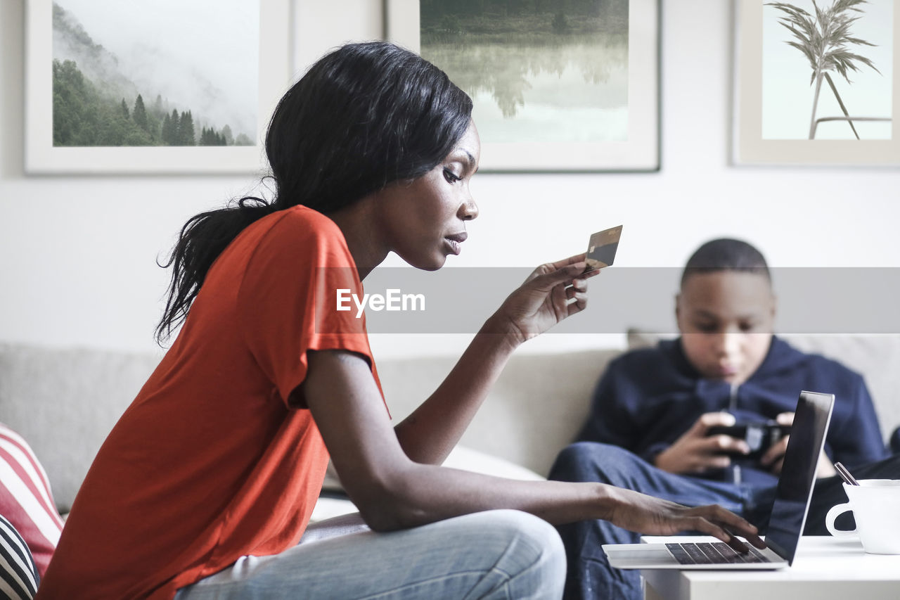 sitting, real people, communication, technology, wireless technology, three quarter length, two people, child, boys, casual clothing, connection, table, males, men, furniture, side view, childhood, computer, indoors, laptop, using laptop, teenage boys