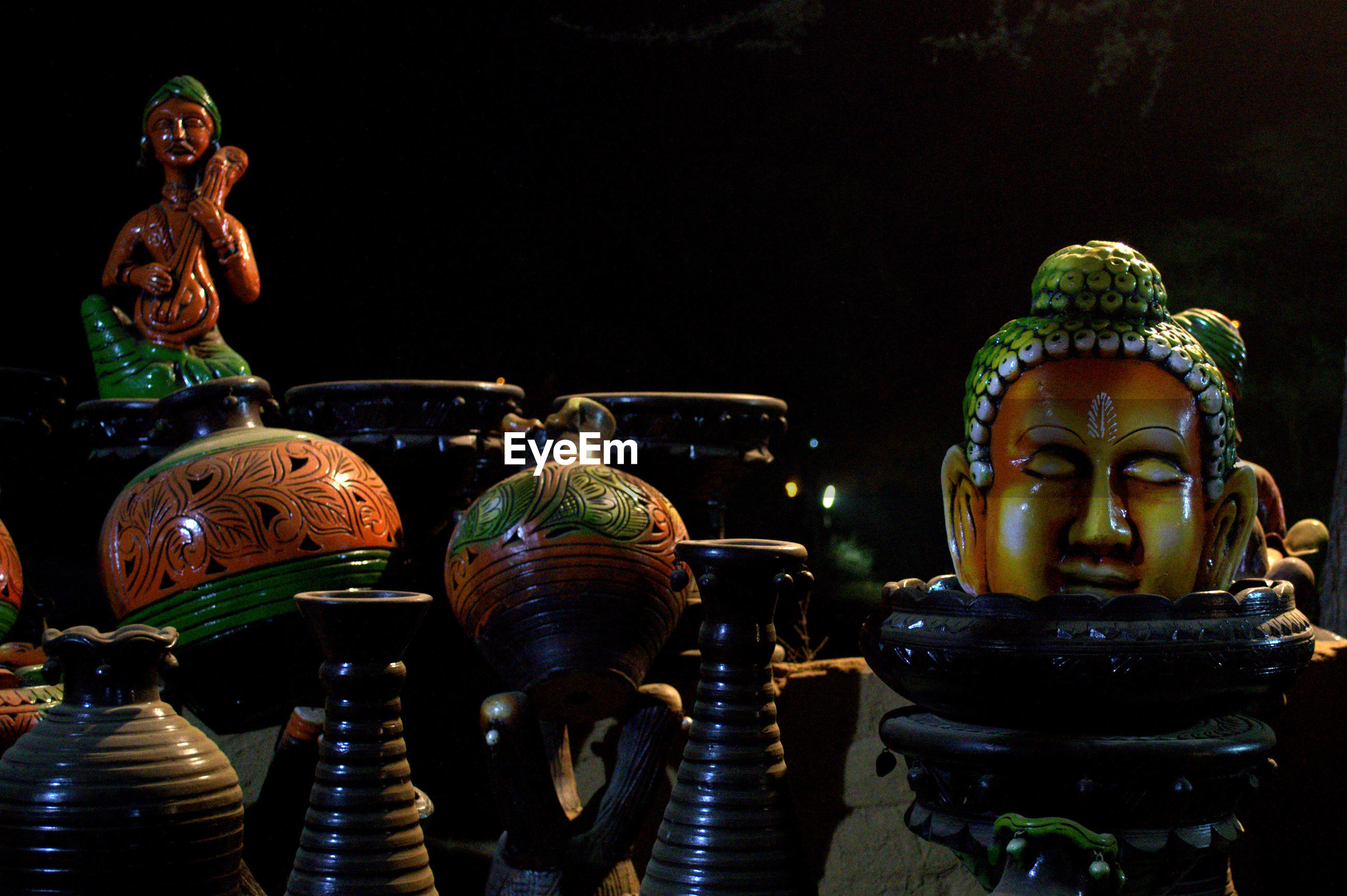 Close-up of buddha statues against black background