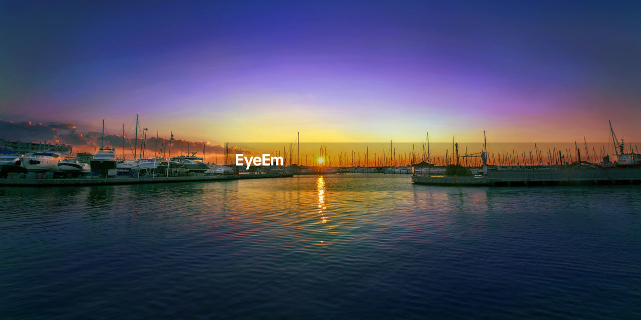 nautical vessel, water, transportation, mode of transport, reflection, moored, sunset, boat, harbor, sky, no people, nature, waterfront, outdoors, mast, travel destinations, tranquility, sea, beauty in nature, scenics, yacht, sailboat, building exterior, night, architecture, city