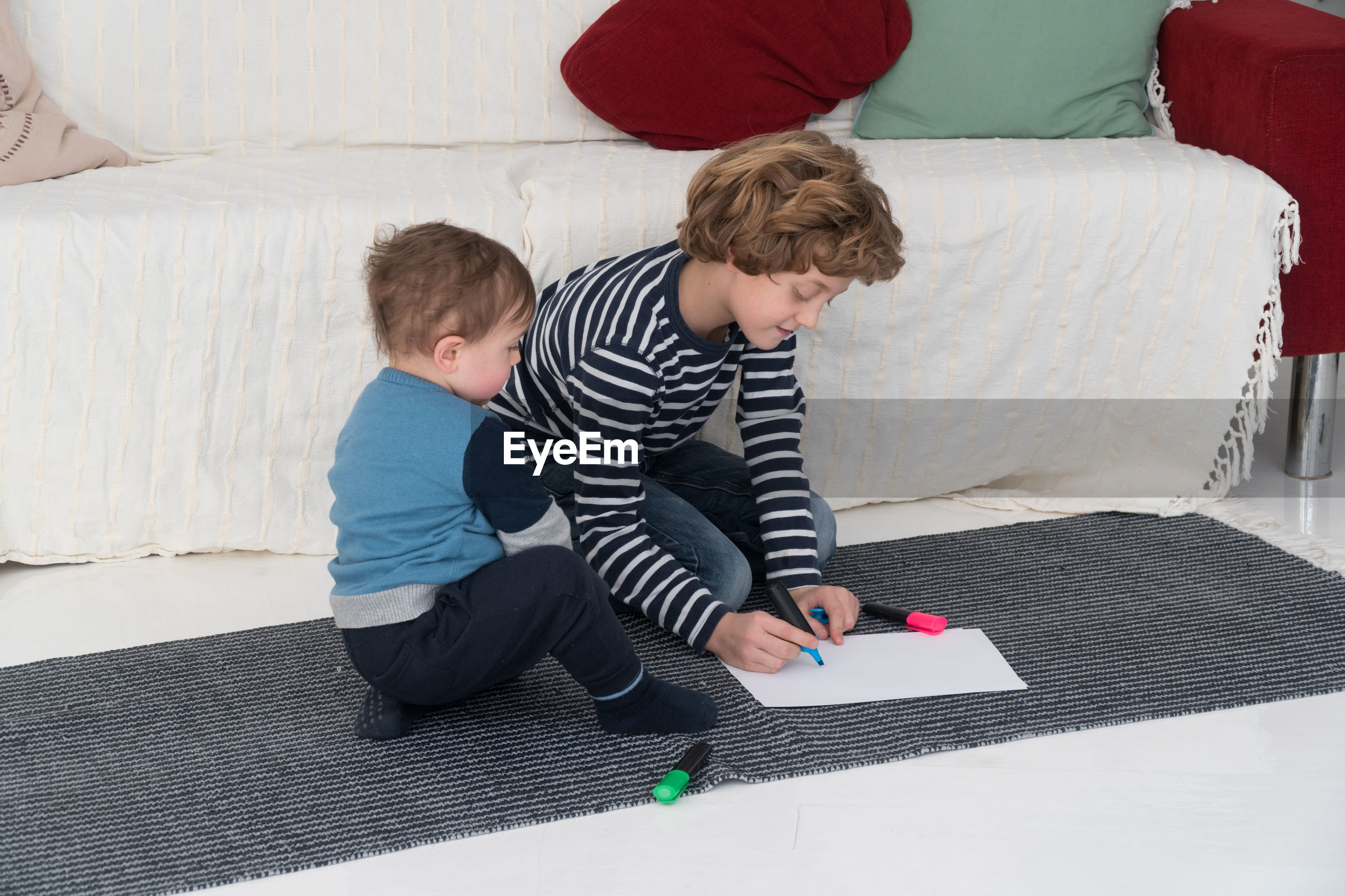 Boy drawing on paper while kneeling by brother on carpet at home
