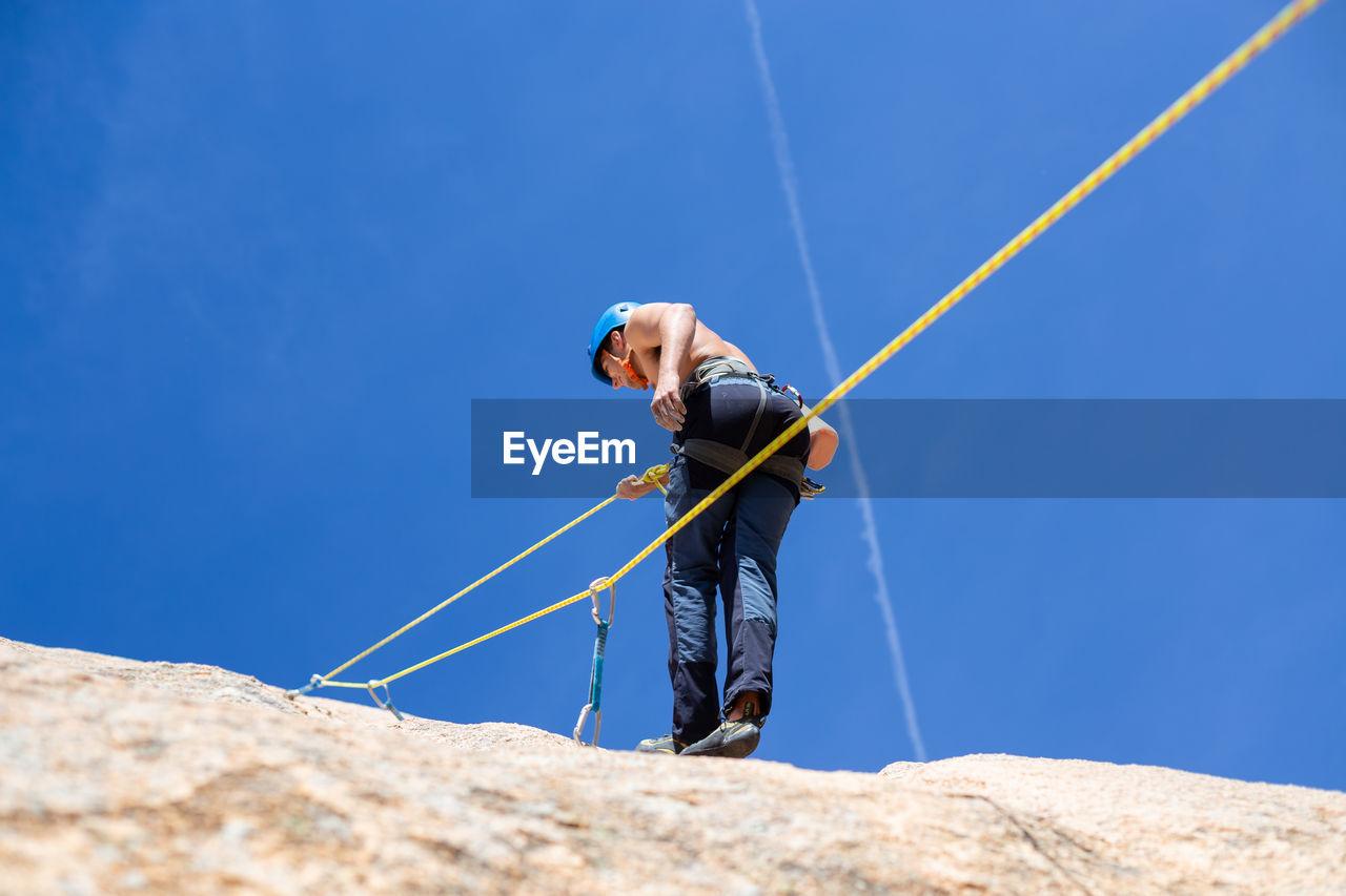 Rear view of shirtless man climbing rock