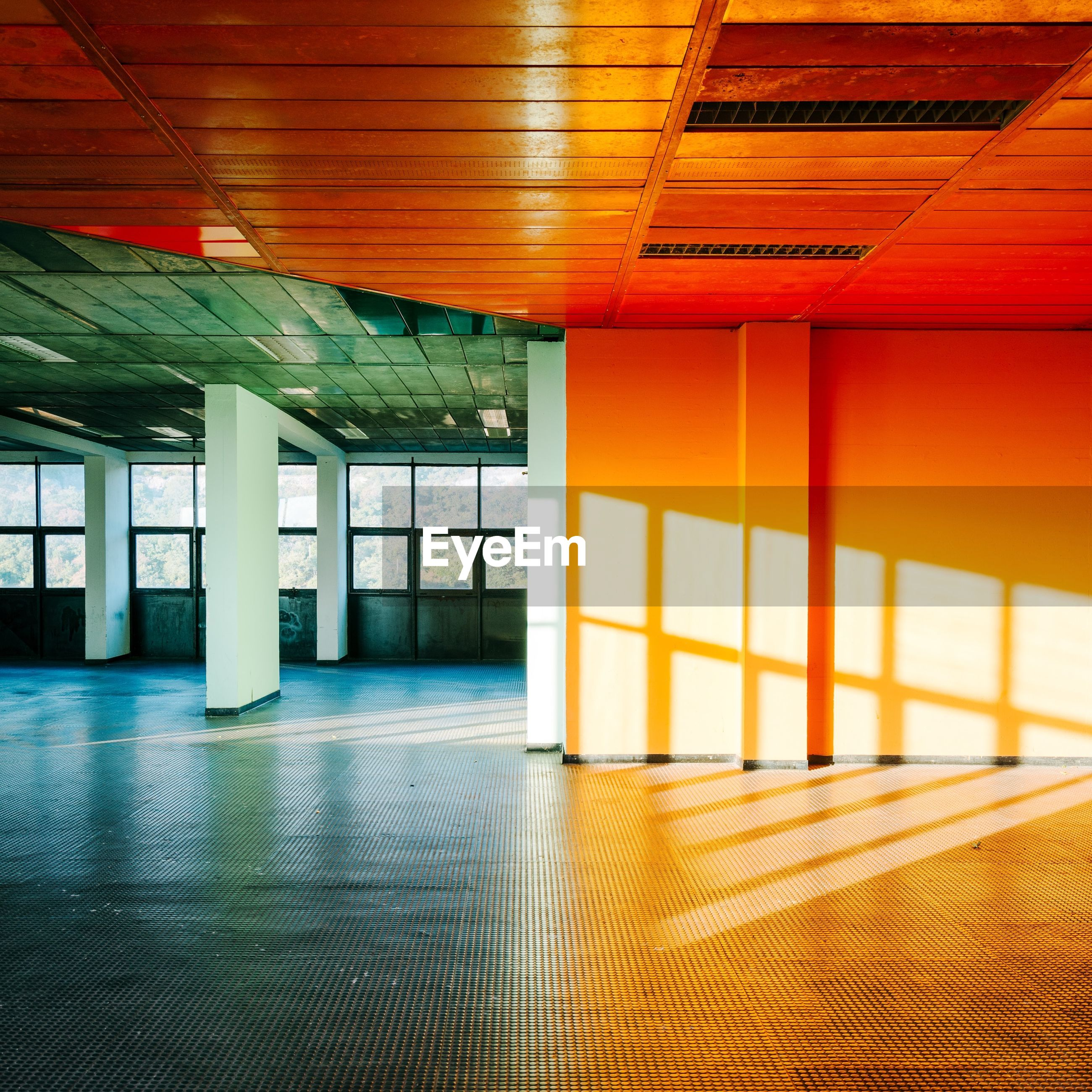 architecture, indoors, built structure, flooring, ceiling, empty, no people, architectural column, building, window, orange color, absence, reflection, transportation, illuminated, corridor, arcade, day, sunlight, modern, station