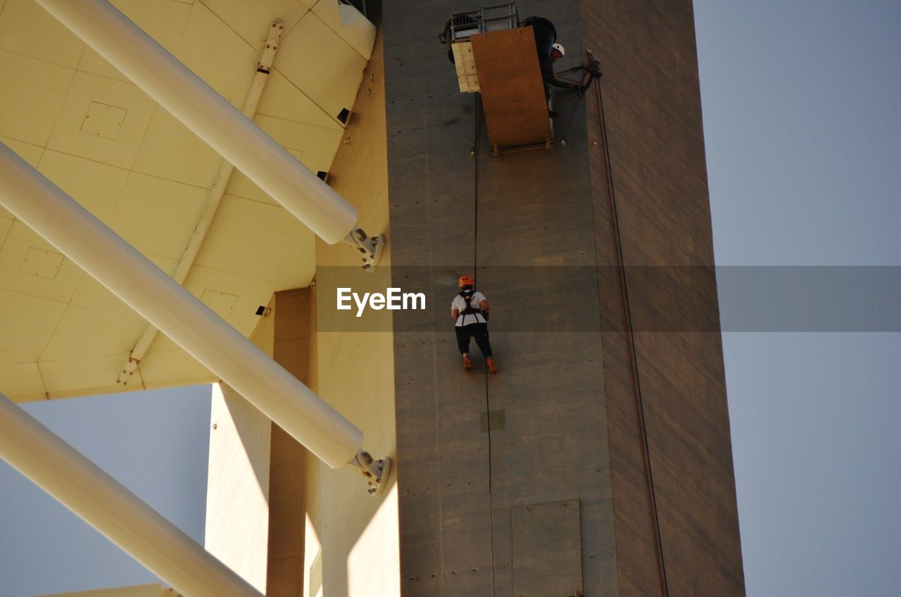 architecture, built structure, building exterior, real people, occupation, men, building, day, working, protection, people, rear view, safety, outdoors, protective workwear, full length, standing, development, uniform