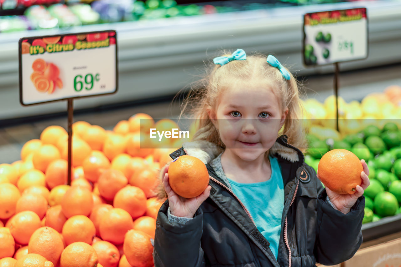 Cute girl holding orange standing in supermarket