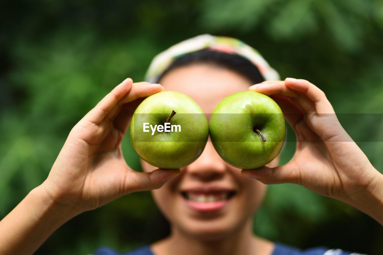 Close-Up Of Woman With Eyes Covered By Apples